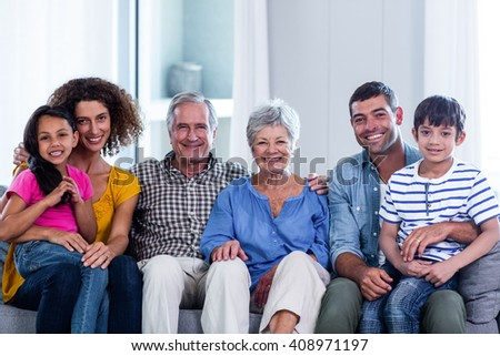 Portrait of happy family sitting together on sofa at home - stock photo