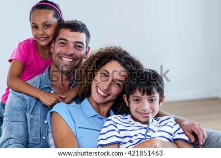 Portrait of happy family sitting together on sofa in living room - stock photo