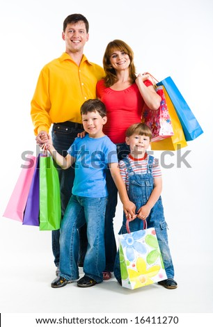 Portrait of happy family standing and holding bags while looking at camera with smiles - stock photo