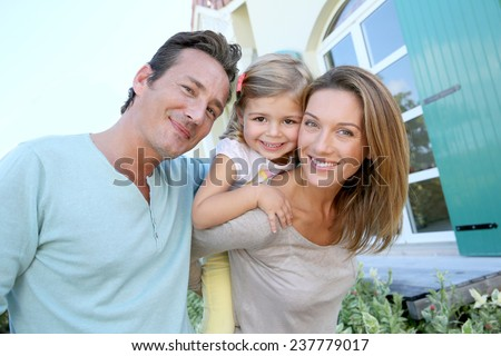 Portrait of happy family standing in front of house - stock photo