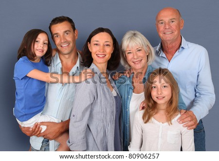 Portrait of happy family standing ion grey background - stock photo