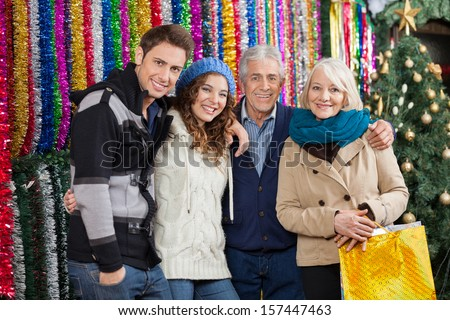 Portrait of happy family standing together against tinsels at Christmas store - stock photo