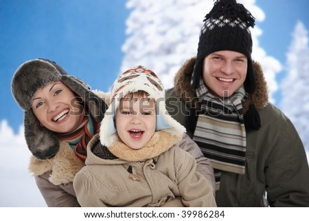 Portrait of happy family together outdoor in snow on a cold winter day, laughing, smiling. - stock photo