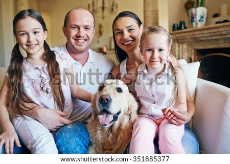 Portrait of happy family with dog - stock photo