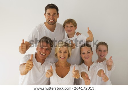 Portrait of happy family with grandparents, parents and grandchildren, smiling and gesturing thumbs up in a white atmosphere. - stock photo