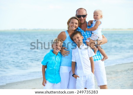Portrait of happy family with kids standing on the beach. - stock photo