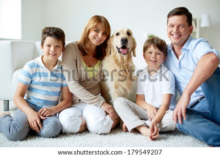 Portrait of happy family with their pet having rest at home - stock photo