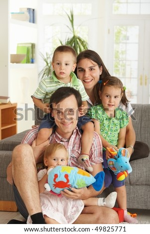 Portrait of happy family with three children at home, cuddling, looking at camera, smiling. - stock photo