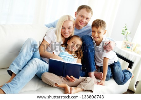 Portrait of happy family with two children looking at camera - stock photo