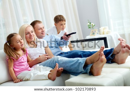Portrait of happy family with two children sitting on sofa and watching TV - stock photo