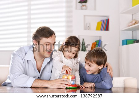 Portrait of happy  father and his children playing at home - stock photo