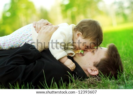 portrait of happy father and son on the grass - stock photo
