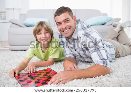 Portrait of happy father and son playing checker game while lying on fur at home - stock photo