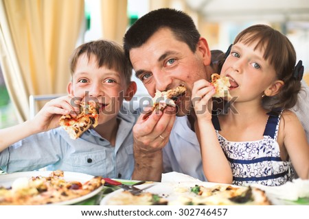 Portrait of happy father with children eating pizza - stock photo