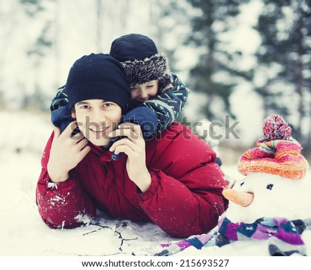 portrait of happy father with his son outside with snowman close up - stock photo