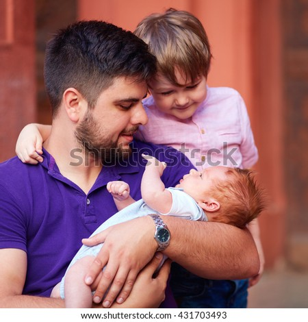 portrait of happy father with newborn baby and son - stock photo