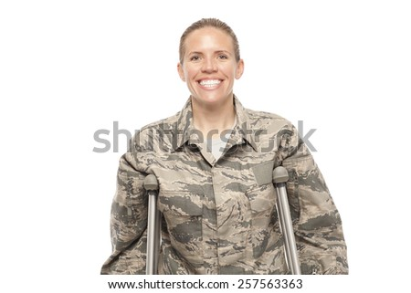 Portrait of happy female airman on crutches against white background - stock photo