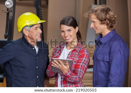 Portrait of happy female carpenter using digital tablet while standing by coworkers in workshop - stock photo