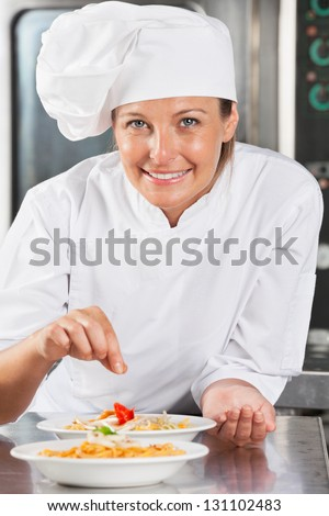 Portrait of happy female chef adding spices to food at commercial kitchen counter - stock photo