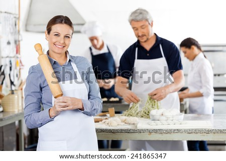 Portrait of happy female chef holding rolling pin while colleagues preparing pasta at commercial kitchen - stock photo