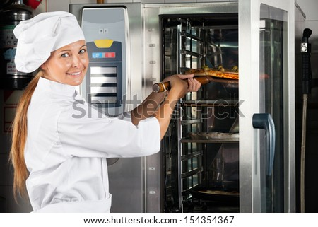 Portrait of happy female chef placing pizza in oven at commercial kitchen - stock photo