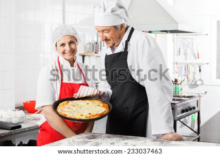 Portrait of happy female chef standing by colleague holding pizza pan at commercial kitchen - stock photo