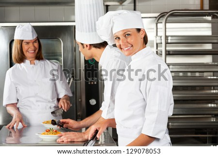 Portrait of happy female chef with colleagues communicating in background at commercial kitchen - stock photo