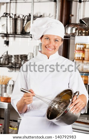 Portrait of happy female chef with wire whisk and mixing bowl at commercial kitchen - stock photo