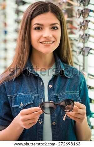 Portrait of happy female customer buying a new glasses at optician store. - stock photo
