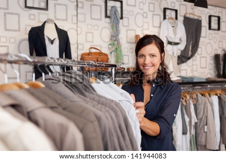 Portrait of happy female customer choosing shirt in clothing store - stock photo
