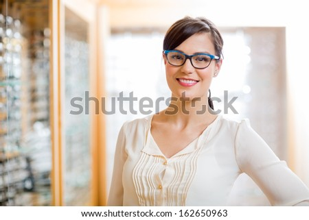 Portrait of happy female customer wearing glasses in store - stock photo