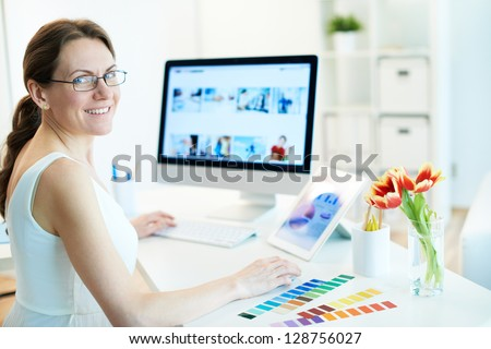 Portrait of happy female designer working and looking at camera - stock photo