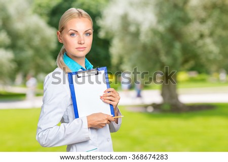 Portrait of happy female doctor holding blank paper on clipboard  - stock photo