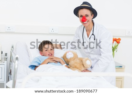Portrait of happy female doctor in clown costume with sick boy in hospital bed - stock photo