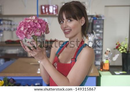 Portrait of happy female florist holding pink hydrangea in flower shop - stock photo