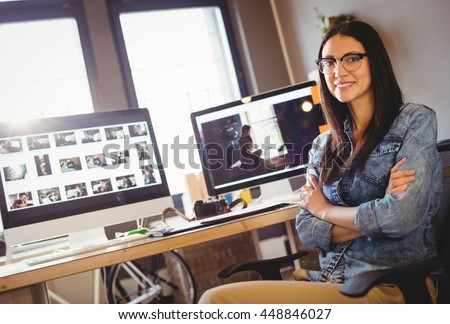 Portrait of happy female graphic designer sitting with arms crossed at office - stock photo