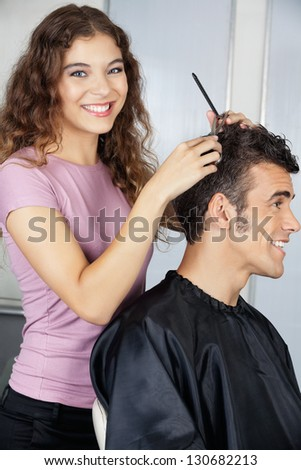 Portrait of happy female hairdresser cutting clients hair in salon - stock photo