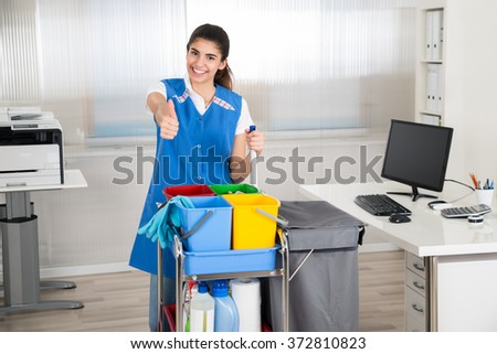 Portrait of happy female janitor with cleaning equipment showing thumbs up in office - stock photo