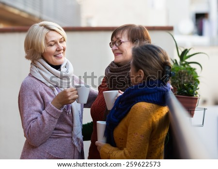 Portrait of happy female pensioners drinking coffee at patio - stock photo
