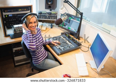 Portrait of happy female radio host at sound mixer desk in studio - stock photo