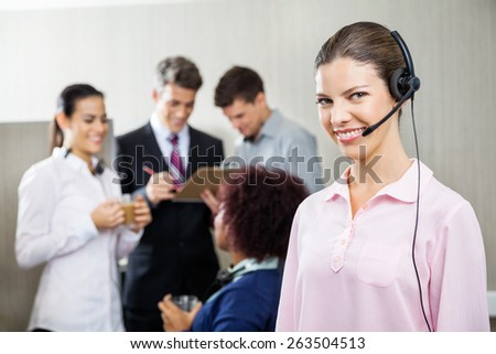 Portrait of happy female service agent standing while team discussing in background at call center - stock photo