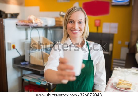 Portrait of happy female shop owner holding glass in bakery - stock photo