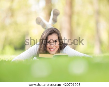 Portrait of happy female student reading a book on a nice and sunny spring day. Young woman is lying on the grass in a park and smiling to camera.  - stock photo
