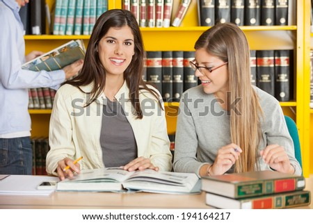 Portrait of happy female student with friend sitting at table in university library - stock photo