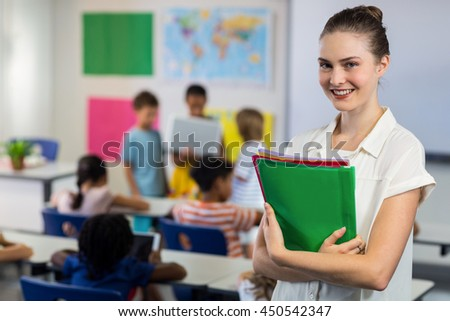 Portrait of happy female teacher with files standing in classroom - stock photo