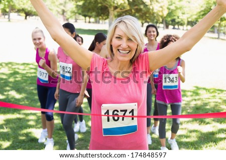 Portrait of happy female winner of breast cancer marathon race at park - stock photo