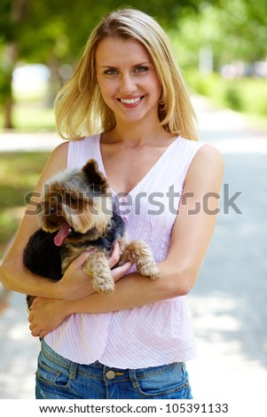 Portrait of happy female with fluffy pet looking at camera in park - stock photo