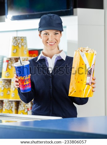 Portrait of happy female worker holding popcorn and drink at cinema concession counter - stock photo