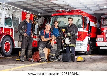 Portrait of happy firefighter's team with equipment against trucks at fire station - stock photo