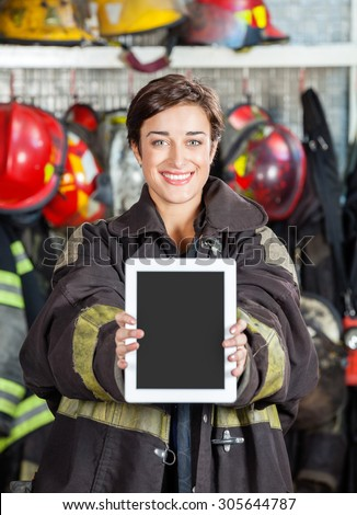 Portrait of happy firewoman showing digital tablet at fire station - stock photo